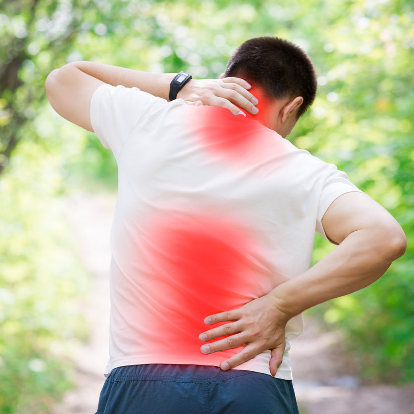 Man with back pain, injury while running, trauma during workout, outdoors concept